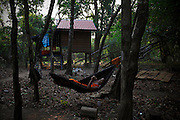 A novice monk relaxes in a hammock at their residence in the Monks Community Forest.