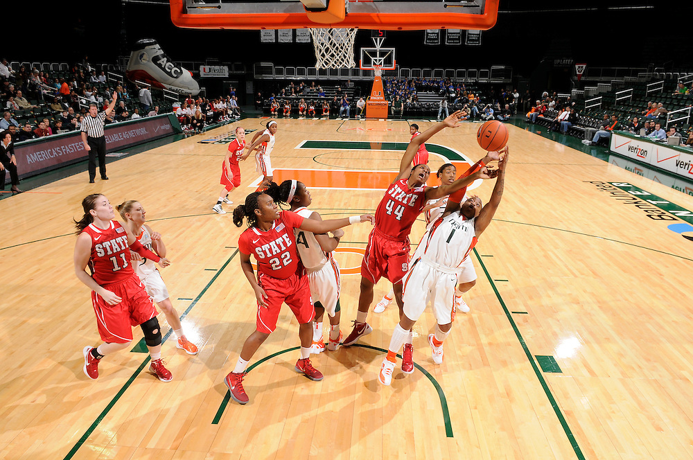 January 5, 2012: Kody Burke #44 of North Carolina State reaches for a rebound over Riquna Williams #1 of Miami during the NCAA basketball game between the Miami Hurricanes and the North Carolina State Wolfpack at the BankUnited Center in Coral Gables, FL. The Hurricanes defeated the Wolfpack 78-68.