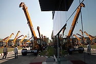 Employees walk past  lined up finished machines parked infront of the factory, at JCB India ltd, in Faridabad, Haryana India, on Tuesday, October 4 2011.  Photographer: Prashanth Vishwanathan/Bloomberg News