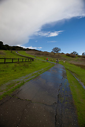 People exercise after a rain shower on the pathway to The Dish, part of radiotelescope with a 150 foot parabolic antennae used for astronomical observations, located in the Stanford Foothills on the campus of Stanford University, Stanford, California, United States of America.