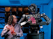 Roboticist Rodney Brooks of the MIT Artificial Intelligence Laboratory shares a slinky moment with his creation, Cog (short for cognitive), the robot he has been developing since 1993. Brooks is less concerned with making it mobile than with creating a system that will let the robot reliably tell the difference between static and social objects; for instance a rock and a person. In the resolution of such apparently simple distinctions, Brooks suggests, is a key to understanding at least one type of human learning. Cambridge, MA. From the book Robo sapiens: Evolution of a New Species, page 62-63.