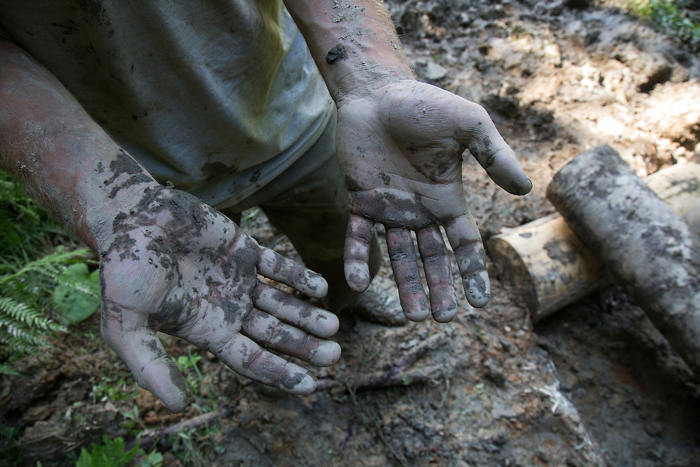 Trail designer Jonathan Baxter shows his muddy hands after working all day to build a turnpike on a boggy site along the Transcaucasian Trail.