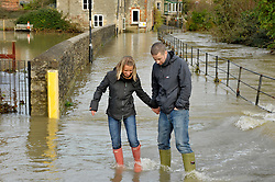 © Licensed to London News Pictures. 25/11/2012. Malmesbury, UK. Picture of Lydia Carver and Matt Jupe wading through flooding in the centre of Malmesbury.  25 November 2012..Photo credit : Simon Chapman/LNP