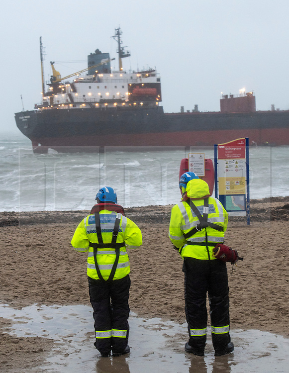 © Licensed to London News Pictures. 18/12/2018. Falmouth, UK. Members of a search and rescue team watch Russian cargo ship Kuzuma Minin, run aground on the reef off Gyllyngvase beach in Falmouth Bay in the early hours this morning. The Falmouth lifeboat and the Coastguard helicopter are involved in the major incident.  Photo credit: Mark Hemsworth/LNP