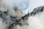 Fog swirls around the rocky cliffs in Yosemite National Park.