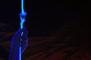 A hand grasps on to a rope that is frayed down to its last thread.Black light