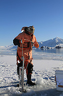 Marine chemist Melissa Chierici (Institute of Marine Research) samples seawater beneath frozen fjord; Kongsfjorden, Svalbard, Norway.
