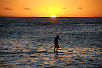Paddling on the ocean during a Kuhio sunset in Hawaii.