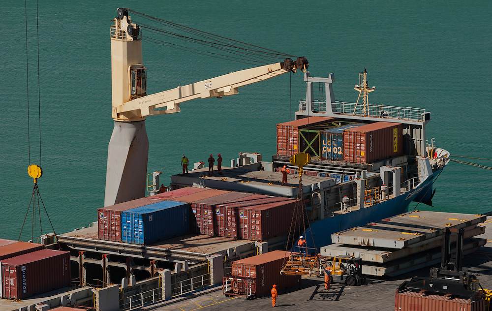 A ship deck crane unloads a containers onto the wharf at Lyttelton Harbour, New Zealand, assisted by dock workers