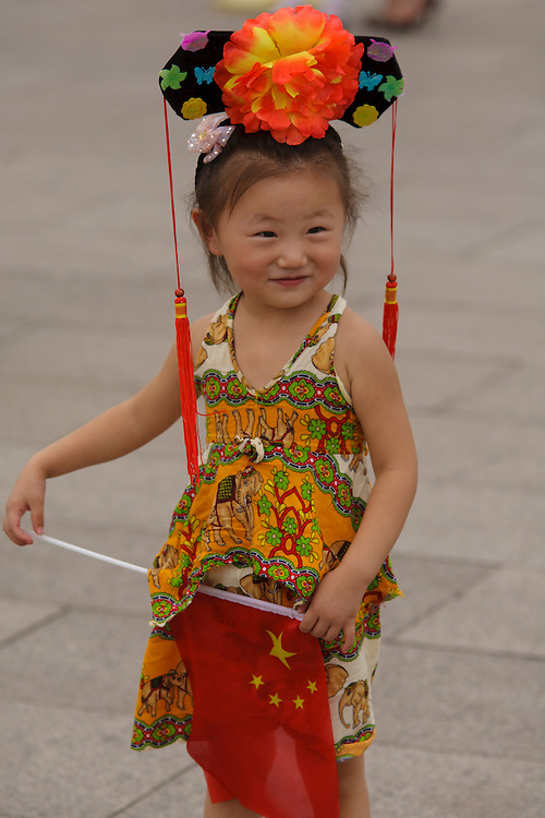 A girl wearing chines costumes poses for photo in Tian'anmen square