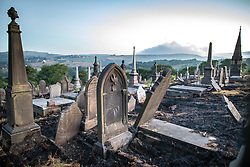 "© Licensed to London News Pictures . 28/06/2018 . Saddleworth , UK . View of smoke on hills across Saddleworth moor across scorched earth in Saddleworth Graveyard , where fire burned through dry grass in the late hours of Wednesday 27th June (yesterday) and had to be extinguished by firefighters . The army are being called in to support fire-fighters , who continue to work to contain large wildfires spreading across Saddleworth Moor and affecting people across Manchester and surrounding towns . Very high temperatures , winds and dry peat are hampering efforts to contain the fire , described as "" unprecedented "" by police and reported to be the largest in living memory . Photo credit: Joel Goodman/LNP"
