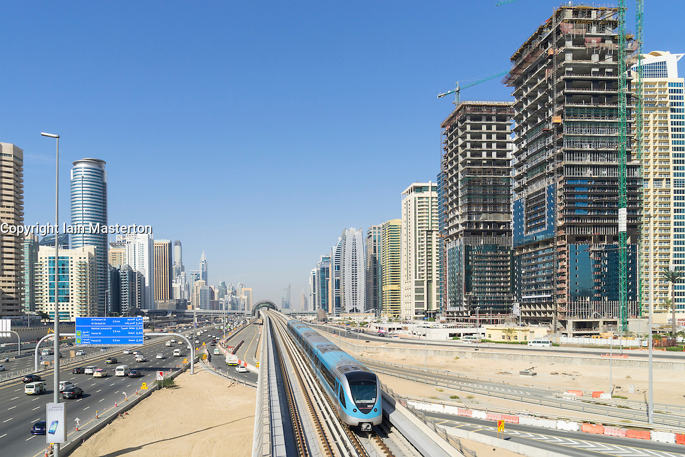 Metro train and skyline of Dubai at Jumeirah Lakes Towers (JLT)  in Dubai United Arab Emirates