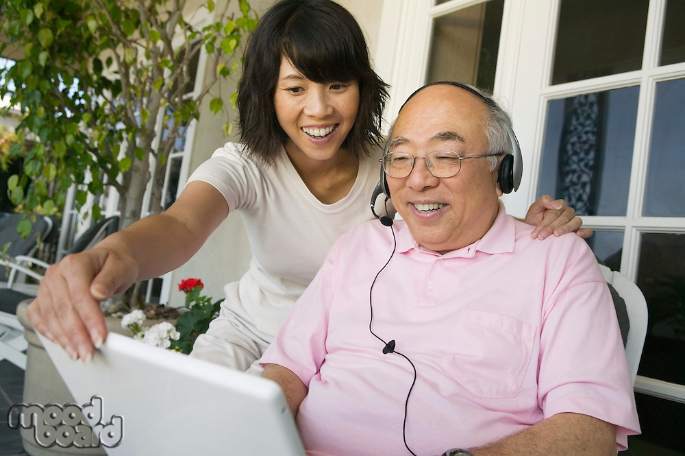 Woman assisting father wearing headset and using laptop on porch