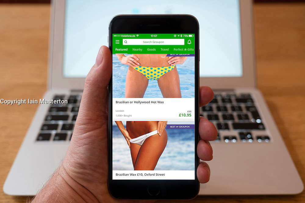 Using iPhone smartphone to display Groupon app with discounted spa treatments