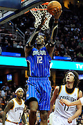 Dec. 28, 2010; Cleveland, OH, USA; Orlando Magic center Dwight Howard (12) lays in a basket over Cleveland Cavaliers power forward Anderson Varejao (17) during the third quarter at Quicken Loans Arena. The Magic beat the Cavaliers 110-95. Mandatory Credit: Jason Miller-US PRESSWIRE