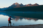 A fisherman carries a fish and rod on the shore of Bowman Lake as sunset illuminates the Rocky Mountains in Glacier National Park, Montana, USA.