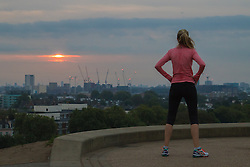 Primrose Hill, London, September 22nd 2016. A runner rests and admires the view from Primrose Hill as the autumn equinox sun rises over London . ©Paul Davey<br /> FOR LICENCING CONTACT: Paul Davey +44 (0) 7966 016 296 paul@pauldaveycreative.co.uk