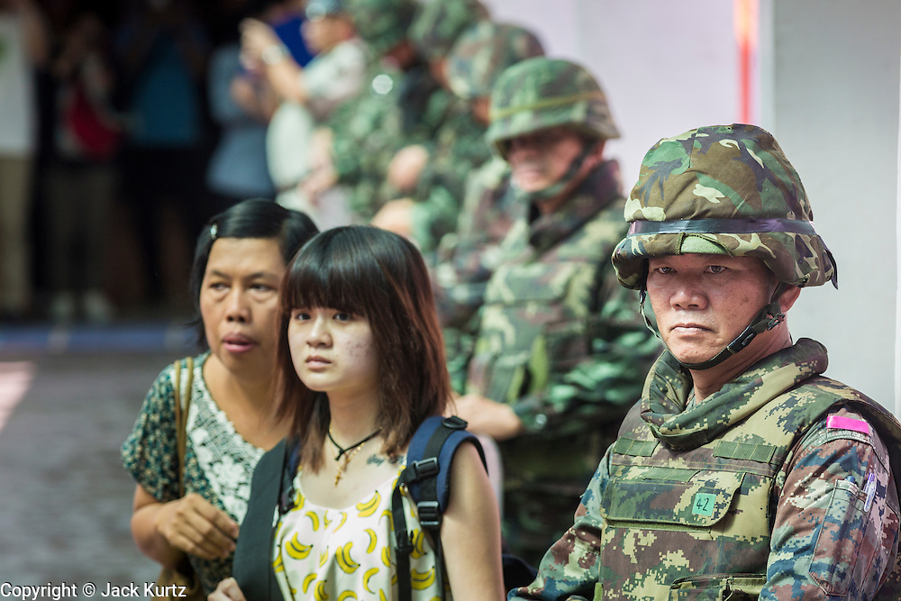 25 MAY 2014 - BANGKOK, THAILAND: Shoppers walk past soldiers stationed near a Bangkok shopping mall. Public opposition to the military coup in Thailand grew Sunday with thousands of protestors gathering at locations throughout Bangkok to call for a return of civilian rule and end to the military junta.     PHOTO BY JACK KURTZ