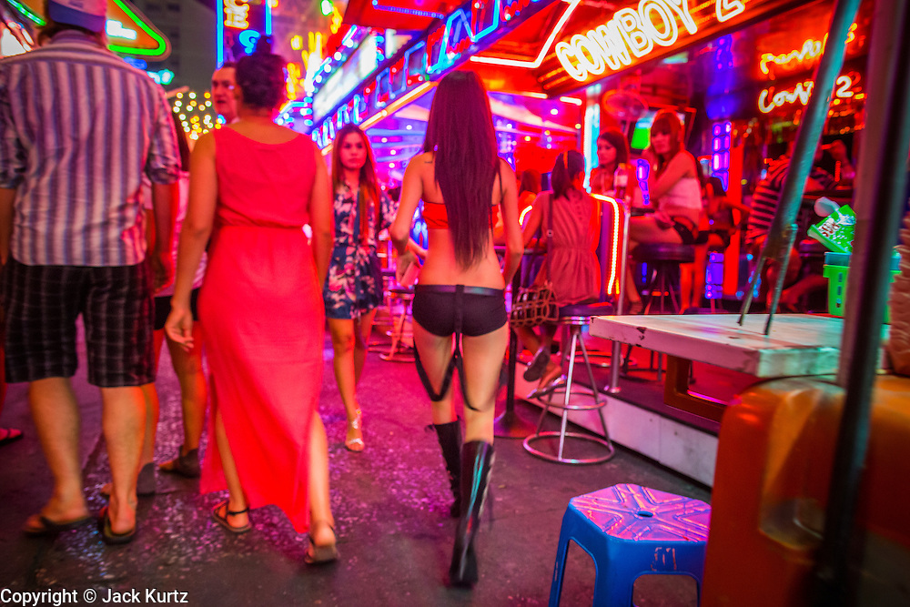 "21 JANUARY 2013 - BANGKOK, THAILAND:  A woman who works in a ""go-go bar"" walks down Soi Cowboy, a red light district in Bangkok. Prostitution in Thailand is technically illegal, although in practice it is tolerated and partly regulated. Prostitution is practiced openly throughout the country. The number of prostitutes is difficult to determine, estimates vary widely. Since the Vietnam War, Thailand has gained international notoriety among travelers from many countries as a sex tourism destination. One estimate published in 2003 placed the trade at US$ 4.3 billion per year or about three percent of the Thai economy. It has been suggested that at least 10% of tourist dollars may be spent on the sex trade. According to a 2001 report by the World Health Organisation: ""There are between 150,000 and 200,000 sex workers (in Thailand).""  PHOTO BY JACK KURTZ"