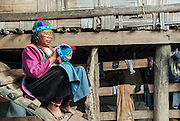 A woman weaves a tourist hat on the steps of her home in the Mae Hong Son Province of Northern Thailand. She is from the Kayan Tribe, a group of refugees from fighting in Burma.