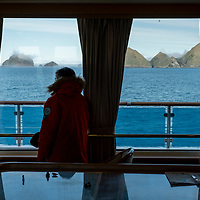 A guest in the observation lounge of the National Geographic Orion looks ahead to Elsehul, a bay on the northwest coast of South Georgia Island.
