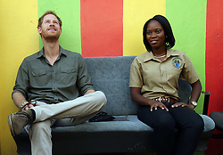 Prince Harry sits next to a local woman during a visit to the hillside village of Vermont on the island of Saint Vincent, St Vincent and the Grenadines, during the second leg of his Caribbean tour.