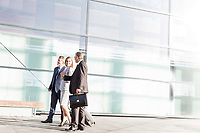 Business people walking while talking in airport