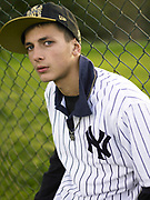 Young man wearing NY Yankees sports t-shirt and baseball cap.
