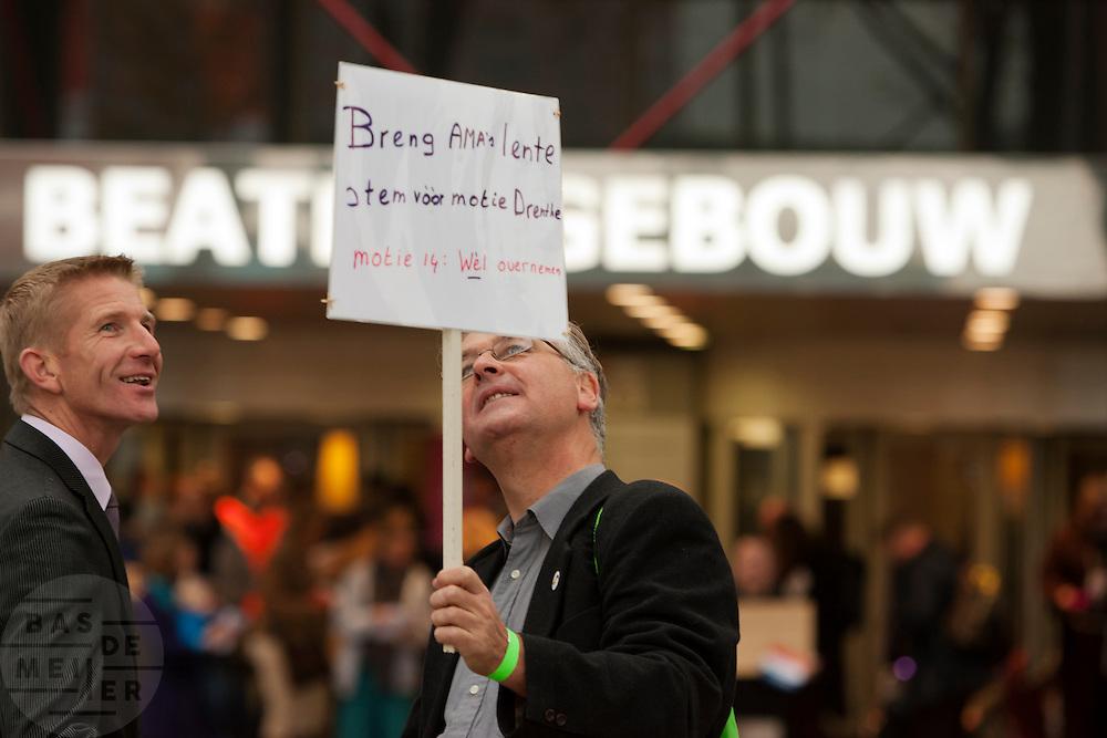 CDA-er Jack de Vries bekijkt een protestbord bij de ingang van het najaarscongres.. In Utrecht houdt het CDA haar partijcongres. Het congres staat voor een groot deel in het teken van de uitzetting van Mauro. <br /> <br /> CDA party member is looking at a sign of a protestor outside the congress in Utrecht.