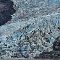 Mendenhall Glacier Terminus Features near Juneau, Alaska<br /> This terminus of Mendenhall Glacier near Juneau shows several glacial features.  At this ablation zone, the tidewater glacier will shed large sheets of ice into Mendenhall Lake.  This process is called calving.  Notice the complex structure of ridges, facets, crevasses and suncups that reflect the color blue.  The black streaks are crushed sediment and rock called moraine.  The vegetation-free rock is the barren zone and the grooves are chatter marks.