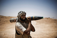 LIBYAN ARAB JAMAHIRIYA, Nalut : A Libyan rebel fighter carring a tank cartridges on the front line by near the southwest village of Gazaia as rebels attack forces loyal to Moamer Kadhafi, on July 28, 2011.ALESSIO ROMENZI