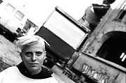 Female traveller with bleached hair, standing by trucks, Berlin, Germany, 2000's,