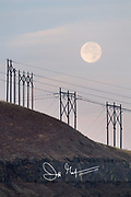 The full moon sets over electrical towers on a mountain.