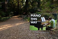 A sign points the way to another performer at the Flower Piano event at the San Francisco Botanical Garden in Golden Gate Park in San Francisco, Tuesday, July 10, 2018. (Photo by D. Ross Cameron)