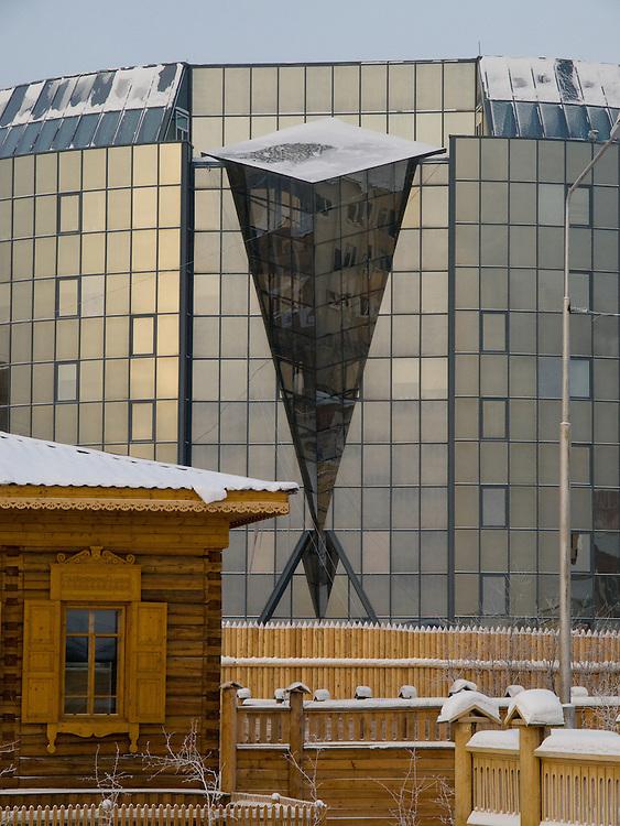 Das Diamanten Museum (Hintergrund) im Kontrast zu dem nachgebauten und historischen Stadtkern aus Holzbauten in der sibirischen Stadt Jakutsk. Jakutsk wurde 1632 gegruendet und feierte 2007 sein 375 jaehriges Bestehen. Jakutsk ist im Winter eine der kaeltesten Grossstaedte weltweit mit durchschnittlichen Winter Temperaturen von -40.9 Grad Celsius. Die Stadt ist nicht weit entfernt von Oimjakon, dem Kaeltepol der bewohnten Gebiete der Erde.<br /> <br /> The Diamond-Museum (background) in contrast to the rebuilt and historical old town in the Siberian city Yakutsk. Yakutsk was founded in 1632 and celebrated 2007 the 375th anniversary. Yakutsk is a city in the Russian Far East, located about 4 degrees (450 km) below the Arctic Circle. It is the capital of the Sakha (Yakutia) Republic (formerly the Yakut Autonomous Soviet Socialist Republic), Russia and a major port on the Lena River. Yakutsk is one of the coldest cities on earth, with winter temperatures averaging -40.9 degrees Celsius.