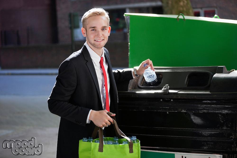 Portrait of young businessman throwing plastic bottles in bin