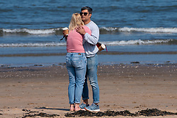 Portobello, Scotland, UK. 25 April 2020. Views of people outdoors on Saturday afternoon on the beach and promenade at Portobello, Edinburgh. Good weather has brought more people outdoors walking and cycling. Police are patrolling in vehicles but not stopping because most people seem to be observing social distancing. Young couple embracing on the beach.   Iain Masterton/Alamy Live News