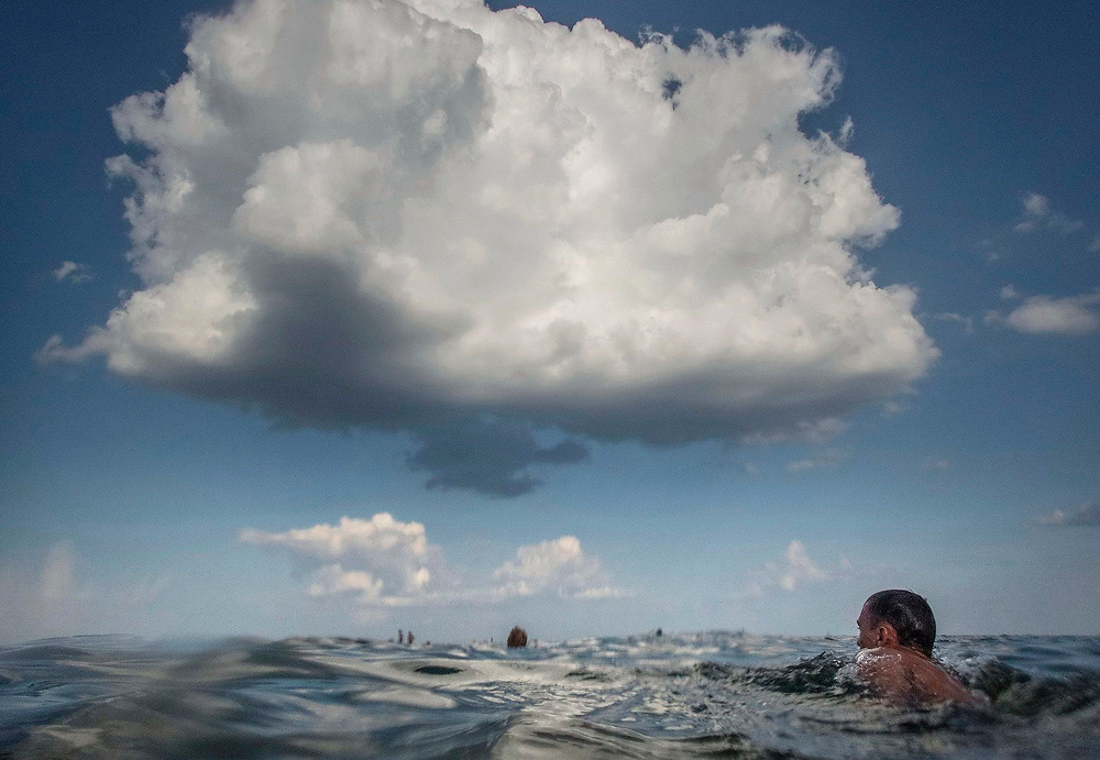 People swimming under a white cloud in the Black Sea, Otrada Beach, Odessa, Ukraine.