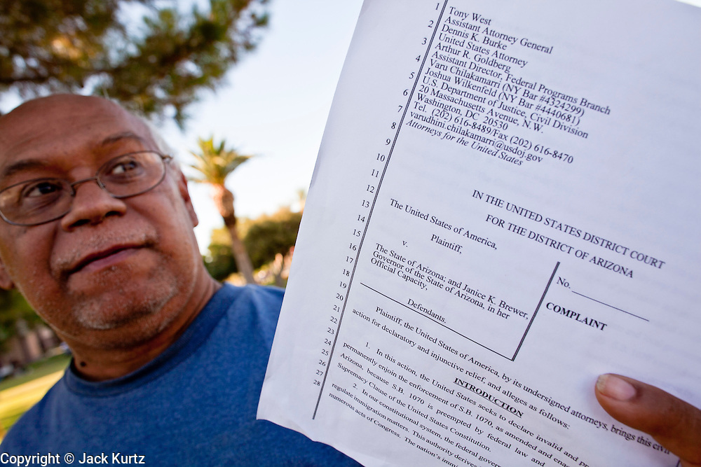July 6 - PHOENIX, AZ: PAUL SANCHEZ, from Phoenix, AZ, holds up a copy of the federal lawsuit against Arizona while he pickets the Arizona State Capitol in Phoenix Tuesday. Immigrant rights' activists have been holding a prayer vigil in opposition to Arizona's tough new anti-illegal immigrant law, SB 1070, which is supposed to take effect on July 29. The bill requires local police and law enforcement agencies to verify the immigration status of people they suspect might be in the US illegally. Opponents of the bill fear it will lead to racial profiling. The US Justice Department announced Tuesday afternoon that they would file suit against Arizona to prevent implementation of SB 1070. They are filing suit on the grounds that immigration enforcement is the exclusive domain of the federal government.       Photo by Jack Kurtz