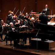 October 4, 2012 - New York, NY : Accompanied by the New York Philharmonic and lead by conductor Alan Gilbert (standing), pianist Emanuel Ax performs Arnold Schoenberg's 'Piano Concerto, Op. 42 (1942) in Lincoln Center's Avery Fisher Hall on Thursday night. CREDIT: Karsten Moran for The New York Times
