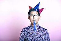 Young Geeky Asian Man wearing many party hats