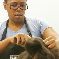 Michelle Munn styles the hair of Liana Slade, 13, at Munn's B Shoppe in Leland, N.C.