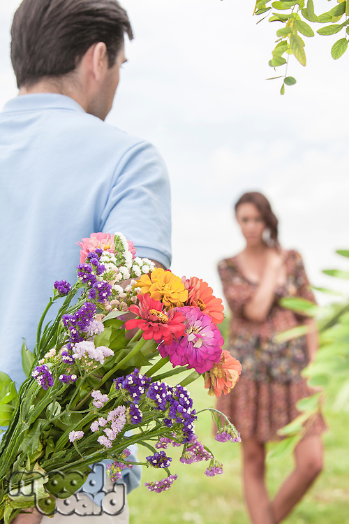 Rear view man surprising woman with bouquet in park