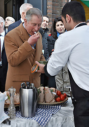 © Licensed to London News Pictures.  27/01/2012. LONDON, UK. Prince Charles (pictured centre) tries Italian food, including a homemade pesto, prepared by Alessio Garau, 29 (pictured right) during a visit to Lower Marsh market near Waterloo. The Prince was visiting with Kirsty Allsopp (pictured back centre) as part of a event for the Prince's Foundation for the Built Environment. Photo credit :  Cliff Hide/LNP
