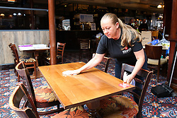 © Licensed to London News Pictures. 03/07/2020. London, UK. LINDY, the Bar Manager cleans a table in The Toll Gate, a Wetherspoon pub in north London as the pub prepares to reopen on 4 July, the 'Super Saturday'. Pubs across the UK closed on 23 March following the coronavirus lockdown. As COVID-19 lockdown restrictions are eased, pubs will reopen on Saturday 4 July. Some pubs are planning to reopen from 6am. Photo credit: Dinendra Haria/LNP