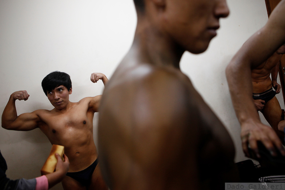 Dante Ajata, left, a professional lawyer, flexes his muscles as his sister Jaqueline Ajata applies make up to his body before a regional bodybuilding championship in La Paz, Saturday, April 10, 2010.