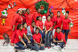 Volunteers and students at Ivanna Eudora Kean High School and Dr. Sharon-Ann McCollum take a picture together with Santa.  The Rotary Club of St. Thomas East hosts Breakfast with Santa at Ivanna Eudora Kean High School where children and their families shared a pancake breakfast, played with gifts, and took pictures with Santa.  St. Thomas, USVI.  5 December 2015.  © Aisha-Zakiya Boyd
