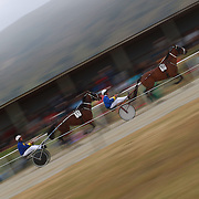 A blur of motion as driver Nathan Williamson and Kacee Jane (left) and Drive Ken Barron and Red and Black pace around the track during the Roxburgh Trotting Club Summer Festival Races, Roxburgh, Otago, New Zealand. 5th January 2012