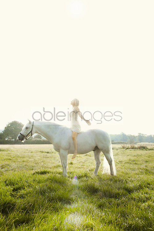 Young Woman Riding Horse in Field