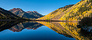 Red Mountain, Hayden Mountain, and golden aspens reflect in Crystal Lake Reservoir on a sunny morning in Uncompahgre National Forest, San Juan Mountains, south of Ouray, Colorado, USA. This image was stitched from multiple overlapping photos.